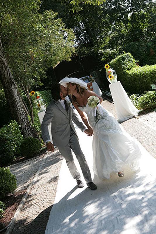 sposi mano nella mano si baciano in giardino