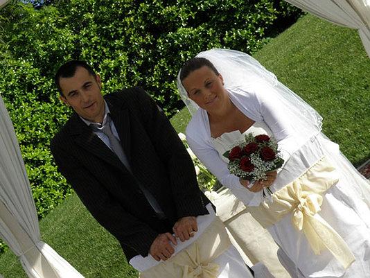 sposi si sotto il gazebo con il bouquet floreale