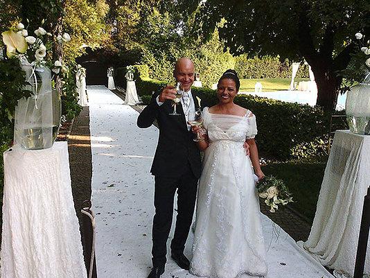 sposi ridono e brindano sul tappetto bianco in gia