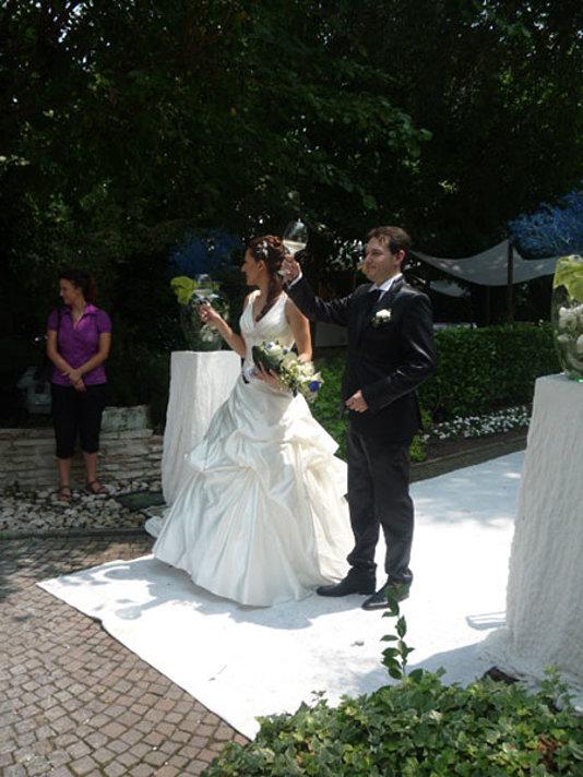 sposa e sposo brindano sul tappeto bianco in corti